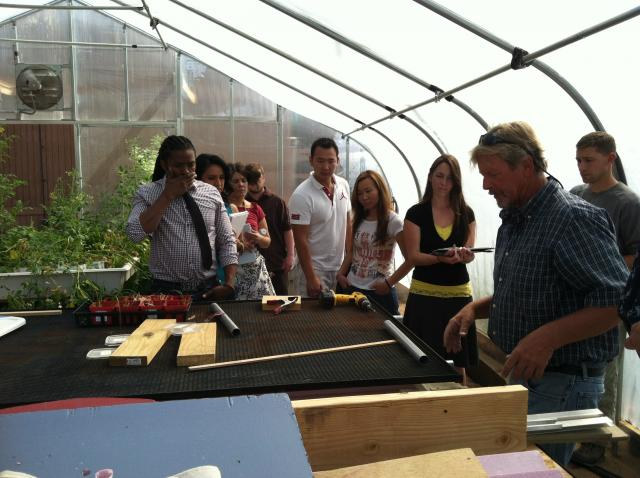 Students in greenhouse talking with groundskeeper